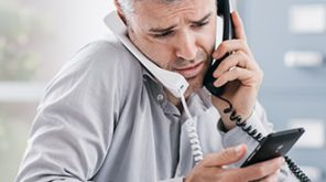Man on two phone calls with a phone in his hand