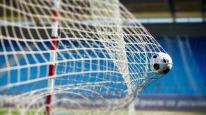Football hitting the back of a football net