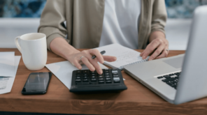 person doing calculations next ot computer (1),